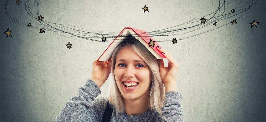 Smiling young woman holding a opened book over her head can't concentrate on learning. Dizzy disheveled girl going crazy with amount of study daydreaming stars and rocket make circles around head.